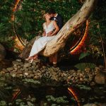 Bride and groom pose in lit ring